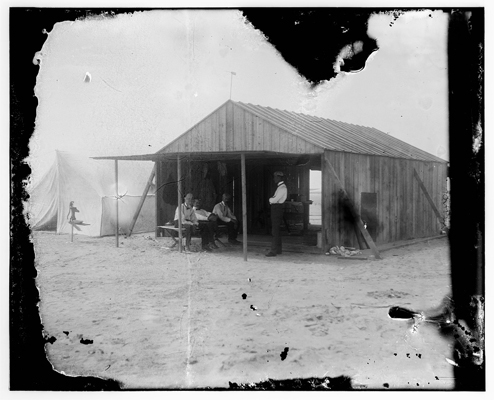Work shed of the Wright Brothers with Ovtave Chanute, Orville Wright and Edward Huffaker (Wilbur standing) — Library of Congress photo  taken by the Wright Brothers