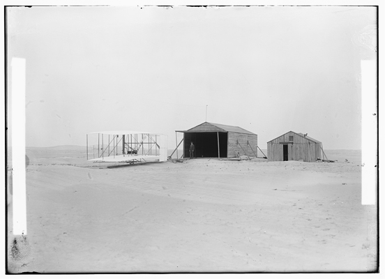 Kill Devil Hills on 24 November 1903, the large building used to house the Wright Flyer with the smaller building which doubled as a workshop and living quarters — Library of Congress photo  taken by the Wright Brothers