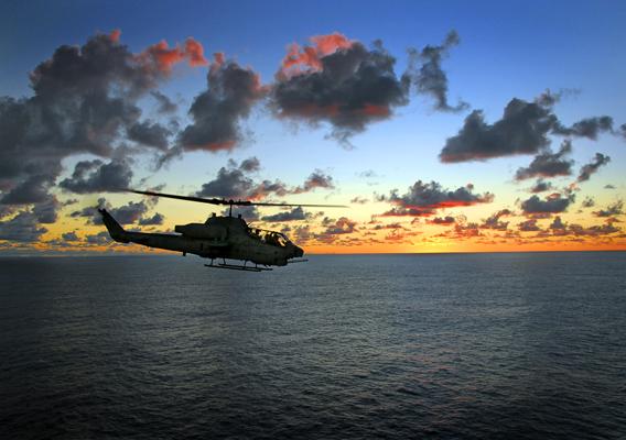 U.S. Marine Corps Bell AH-1A Super Cobra on a sunset pass by the USS Tarawa (LHA 1) — U.S. Navy photo by Mass Comm Spec 3rd Class Danial A. Barker