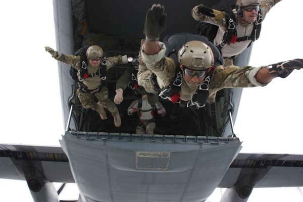 Service men from the EODMU (Explosive Ordnance Disposal) 8 with EOD 1st Class Andrew McCabe in the lead, in free fall deploy training from the rear of a C-130 Hercules — U.S. Navy photo by Sr Chief Aircrew Survival Equipment Man Nathaniel Spencer