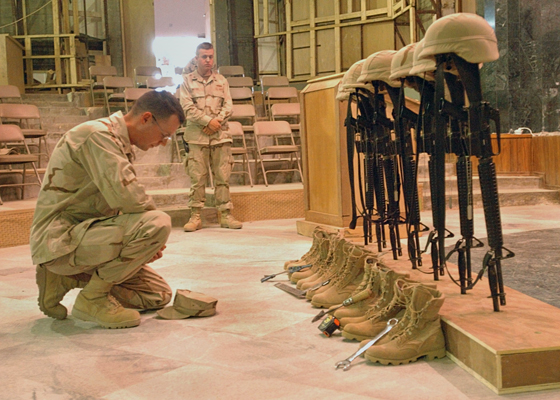 Seabees at a memorial for seven fellow Seabees killed in combat in Fallujah between 30 April and 2 May in 2004. Rifles on bayonets and tools on boots — U.S. Navy photo by Photographer's Mate 2nd Class Eric Powell.
