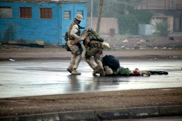 Fallujah 09 Nov 2004. An unidentified Marine and Gunnery Sgt. Ryan Shane (center) recover a fatally wounded Marine. Shane was wounded moments later. U.S. Marine Corps photo by Cpl. Joel A. Chaverri.