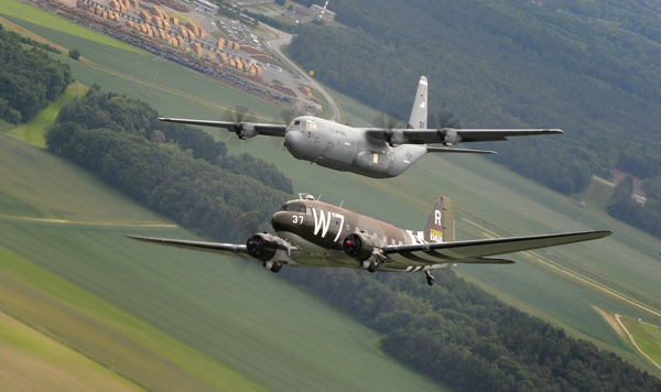 A Douglas C-47 Skytrain, known as Whiskey 7, flies alongside a C-130J Super Hercules from the 37th Airlift Squadron over Germany, May 30, 2014. The C-47 came to Ramstein for a week to participate in base activities with its legacy unit, the 37th Airlift Squadron, before returning to Normandy to recreate its role and drop paratroopers over the original drop zone in Sainte-Mere Eglise, France. (U.S. Air Force photo/Staff Sgt. Sara Keller)