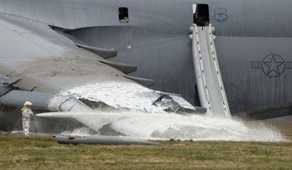 A firefighter hoses down the crash site of a C-5 Galaxy. The aircraft crashed at 6:30 a.m. EDT, on Monday, April 3, 2006, at Dover Air Force Base, Del., just south of the base flightline. All 17 people aboard survived the crash. (U.S. Air Force photo/Doug Curran)