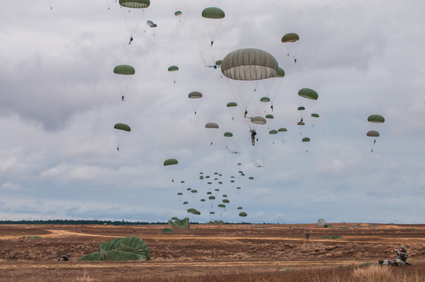 Paratroopers descend on Sicily Drop Zone during the 16th Annual Randy Oler Memorial Operation Toy Drop, at Fort Bragg, N.C., Dec. 7, 2013. While the weather did not cooperate earlier in the day, the rain subsided around midday allowing hundreds of paratroopers to complete their jumps and earn their foreign jump wings while supporting area children in need with a new unwrapped toy. (U.S. Army photo by Timothy L. Hale/Released)