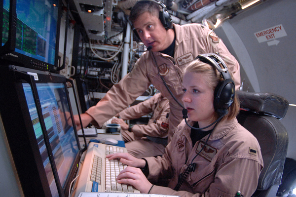 Lt. Col. Doug Sachs and 1st Lt. Beth Brockshus monitor equipment that scans the earth to detect, identify and geolocate signals throughout the electromagnetic spectrum on board an RC-135 Rivet Joint. The two are electronic warfare officers and are two of 34 crew members who fly aboard the RC-135. The crew can forward information in a variety of formats to a wide range of consumers via the plane's extensive communications suite. Colonel Sachs is deployed from Kadena Air Base, Japan, as the 763rd Expeditionary Reconnaissance Squadron commander, and Lieutenant Brockshus is deployed from Offutt Air Force Base, Neb. (U.S. Air Force photo/Master Sgt. Scott Wagers)