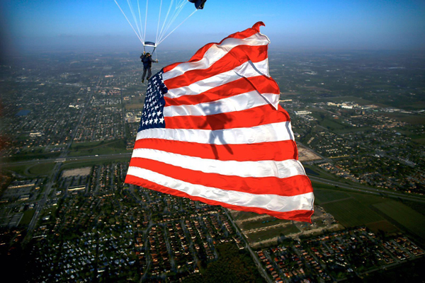 "160226-N-IQ655-172 HOMESTEAD, Fla. (Feb. 26, 2016) - Special Warfare Operator 1st Class Trevor Thompson, member of the U.S. Navy Parachute Team ""The Leap Frogs,"" presents the American flag during a training demonstration at Homestead Air Reserve Base. The Leap Frogs are in Florida preparing for the 2016 show season. (U.S. Navy photo by Jim Woods/Released)"