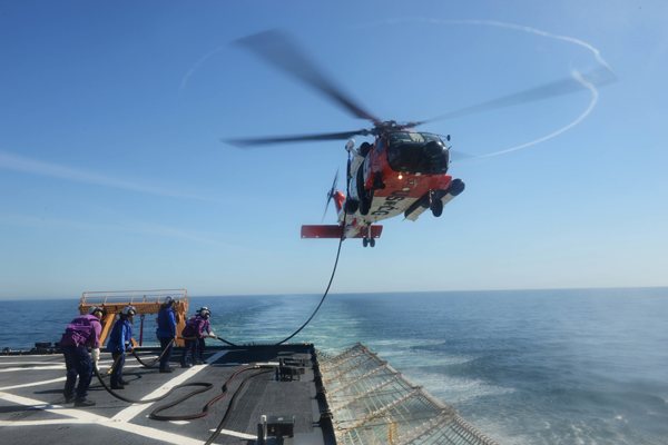 A Coast Guard Air Station Kodiak MH-60 Jayhawk crew conducts a helicopter in-flight refuel evolution with the crew of the Cutter Healy southwest of Kodiak Island, Alaska, July 3, 2015. The HIFR technique allows for Coast Guard helicopter crews to safely refuel from a cutter and extend their search and rescue area, a critical component due to the expansive 44,000 miles of coast that surrounds Alaska. (U.S. Coast Guard photo by Petty Officer 1st Class Kelly Parker)