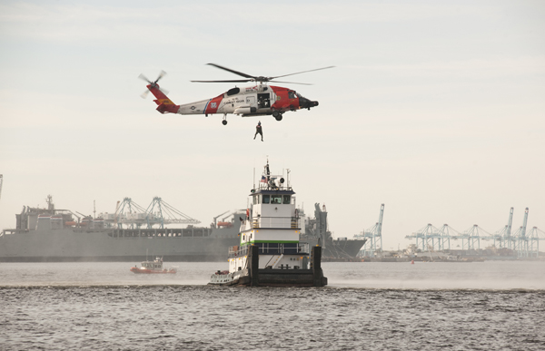 A helicopter crew from Coast Guard Air Station Elizabeth City, N.C., conducts a search and rescue demonstration Thursday, Oct. 22, 2015, on the Elizabeth River near Norfolk, Va. The demonstration was a part of the 16th Annual Towing Vessel Safety Seminar put on by the Coast Guard and Virginia Maritime Association. (U.S. Coast Guard photograph by Coast Guard Auxiliarist Trey Clifton)