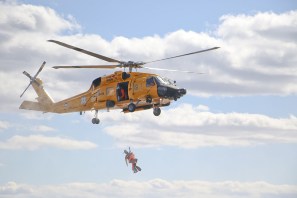 A rescue swimmer hangs below an MH-60 Medium Range Recovery Helicopter Friday, Feb. 26, 2016, during a search and rescue demonstration near Elizabeth City, N.C. U.S. Coast Guard helicopters were painted the retro color scheme to celebrate the Coast Guard's aviation centennial birthday. (U.S. Coast Guard photograph by Lt. Cmdr. Krystyn Pecora)