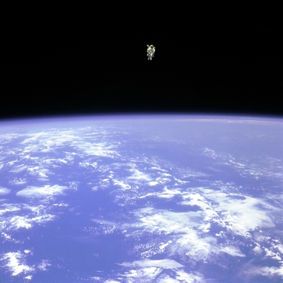 "Mission Specialist Bruce McCandless II, is seen further away from the confines and safety of his ship than any previous astronaut has ever been. This space first was made possible by the Manned Manuevering Unit or MMU, a nitrogen jet propelled backpack. After a series of test maneuvers inside and above Challenger's payload bay, McCandless went ""free-flying"" to a distance of 320 feet away from the Orbiter. This stunning orbital panorama view shows McCandless out there amongst the black and blue of Earth and space."