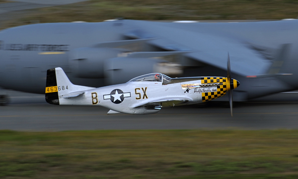 A World War II-era P-51D Mustang fighter aircraft makes a low pass in front of a U.S. Air Force C-17 Globemaster III aircraft at Joint Base Elmendorf-Richardson, Alaska, July 26, 2014, during Arctic Thunder 2014. Arctic Thunder is a biennial event that features more than 40 Air Force, Army and civilian aerial acts and draws crowds of more than 200,000 people. (DoD photo by Justin Connaher, U.S. Air Force/Released)