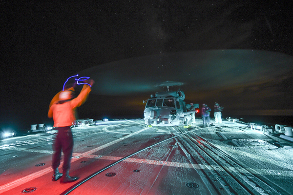 150913-N-SX983-907 ATLANTIC OCEAN (Sept. 13, 2015) Sailors aboard the guided-missile destroyer USS Gravely (DDG 107) refuel an MH-60R Sea Hawk helicopter during night flight operations. Gravely is underway participating in a composite training unit exercise with the Harry S. Truman Carrier Strike Group. (U.S. Navy photo by Mass Communication Specialist Seaman L. E. Skelton/Released)