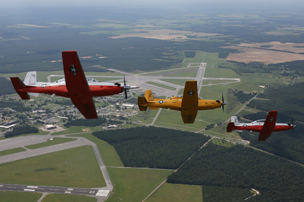 160621-N-HV841-001 - NAS WHITING FIELD, Fla. - Three T-6B Texan IIs bank toward Naval Air Station Whiting Field to help celebrate the arrival of the 148th and final T-6B aircraft to serve as part of Training Air Wing FIVE's primary training fleet. The first T-6 to arrive to Naval Air Station Whiting Field, the centennial color schemed T-6, and the final Texan II to be sent to Training Air Wing FIVE flew three formation passes over the base before landing at the installation's North Field for a ceremony to mark the occasion. U.S. Navy photo by Ensign Antonio More' / released.