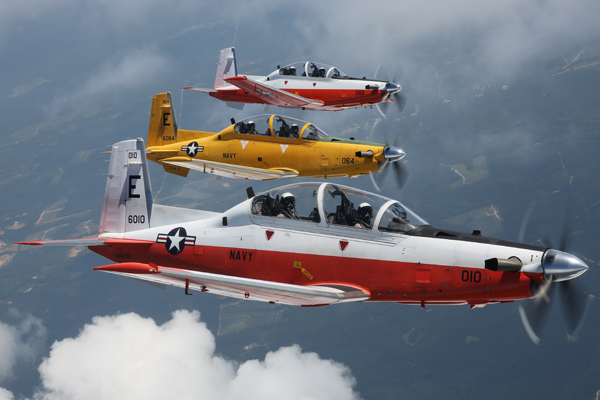 """160621-N-HV841-002 WHITING FIELD, Fla. (June 21, 2016) Three U.S. Navy T-6B """"Texan II"""" aircraft assigned to Training Air Wing FIVE, fly over Naval Air Station Whiting Field in Milton, Florida. Aircraft 166010 is the first T-6B delivered to the United States Navy on August 25, 2009 and aircraft 166260 is the 148th and final T-6B delivered to TRAWING-5 by Beechcraft Defense Company, a subsidiary of Textron Aviation. Since replacing the venerable Beechcraft T-34C """"Turbo Mentor"""" and achieving initial operating capability in April 2010 at Naval Air Station Whiting Field, the T-6B has proven to be a highly dependable turboprop trainer whose primary mission is to train future Navy, Coast Guard and Marine Corps aviators. The three aircraft performed three flyovers of the base before landing to highlight the milestone. U.S. Navy photo by Ensign Antonio More' / released."""