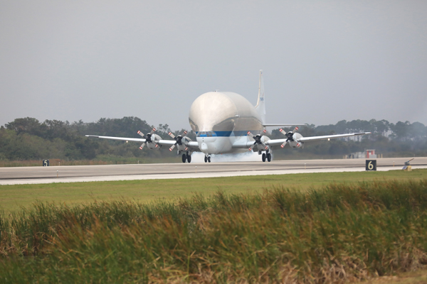 NASA's Super Guppy aircraft touches down at the Shuttle Landing Facility at the agency's Kennedy Space Center in Florida, carrying the Orion crew module adapter structural test article (STA). The STA will be offloaded and transported to the Neil Armstrong Operations and Checkout Building high bay for further testing. Photo credit: NASA/Kim Shiflett