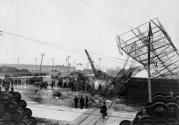 Spectators watch as a crane removes the twisted metal of the crashed Roma. Note how the steering assembly remained caught in a telephone pole on the right. (U.S. Air Force photo)