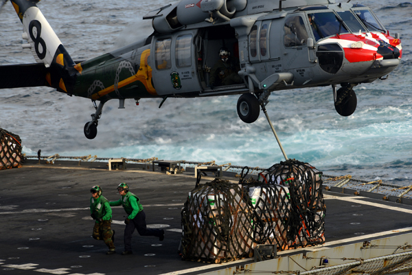 U.S. 5TH FLEET AREA OF RESPONSIBILITY (Feb. 21, 2013) Sailors clear the area as an MH-60S Sea Hawk helicopter from the Eightballers of Helicopter Sea Combat Squadron (HSC) 8 picks up cargo from the flight deck of the Military Sealift Command fast combat support ship USNS Bridge (T-AOE 10) during a replenishment-at-sea with the aircraft carrier USS John C. Stennis (CVN 74). John C. Stennis is deployed to the U.S. 5th Fleet area of responsibility conducting maritime security operations, theater security cooperation efforts and support missions for Operation Enduring Freedom. (U.S. Navy photo by Mass Communication Specialist 2nd Class Kenneth Abbate/Released) 130221-N-OY799-226 Join the conversation http://www.facebook.com/USNavy http://www.twitter.com/USNavy http://navylive.dodlive.mil