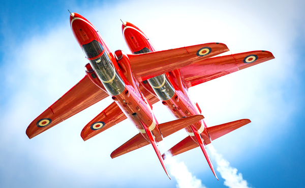 Pictured are two aircraft of the Red Arrows Aerobatic Team flying The Synchro Pair. Reds 6 and 7, perform the highly popular opposition manoeuvres during this latter sections of their shows. The Royal Air Force Aerobatic Team, the Red Arrows, is one of the world's premier aerobatic display teams. Representing the speed, agility and precision of the RAF, the team is the public face of the service. They assist in recruiting to the Armed Forces, act as ambassadors for the United Kingdom and promote the best of British. Flying distinctive Hawk jets, the team is made up of pilots, engineers and essential support staff with frontline, operational experience.