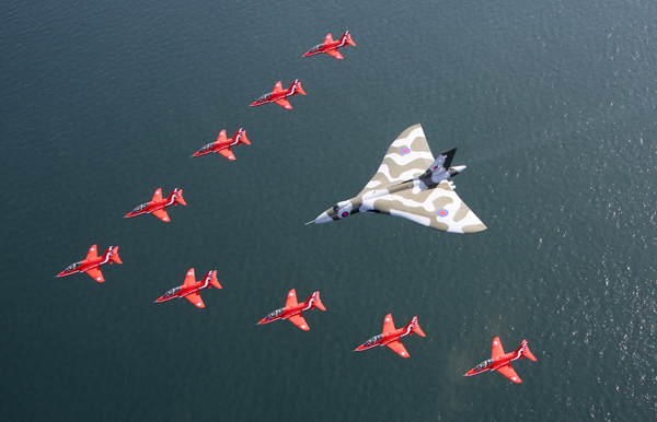 The Red Arrows have flown with the Vulcan bomber for the final time in a show of great British aviation icons. Jets from the Royal Air Force Aerobatic Team performed a flypast with the mighty Cold War aircraft at the Southport Air Show this afternoon (Saturday, September 19th, 2015). Thousands of people cheered and waved as the Red Arrows' nine distinctive British-built Hawk aircraft made a V-shape in front of the Vulcan.