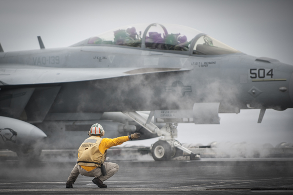 Shooter Lt Wes Smith signals the launching of this EA-18 Growler off of the USS Carl Vinson (CVN 70) — U.S. Navy photo by Mass Comm Spec 2nd Class George M. Bell